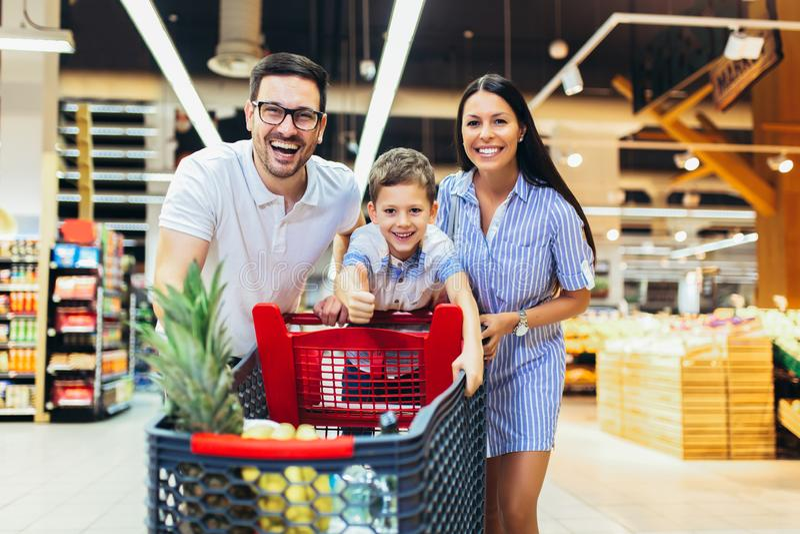 Familie mit Kinder- und des Einkaufswagenskaufender Nahrung am Gemischtwarenladen oder am Supermarkt stockbild