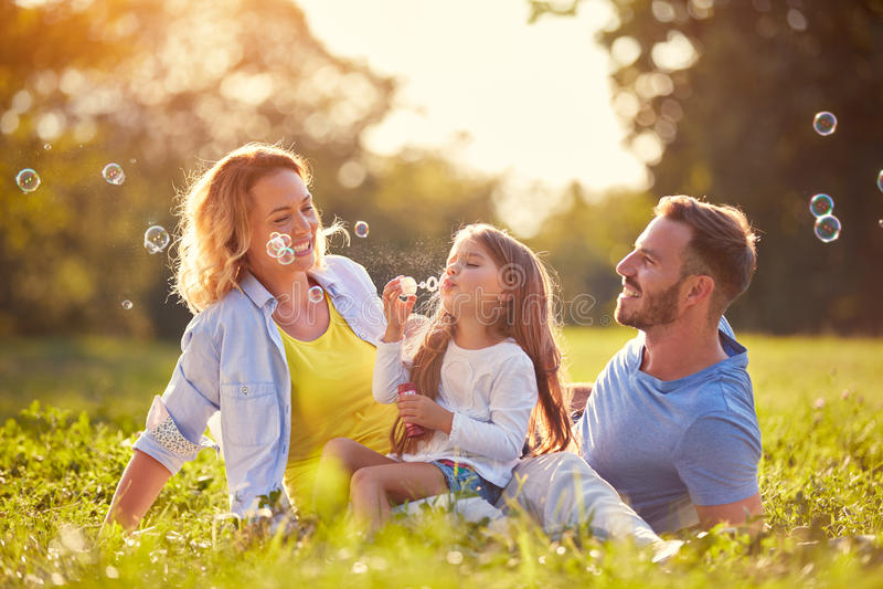 Familie mit Kinderschlagseifenblasen stockbild