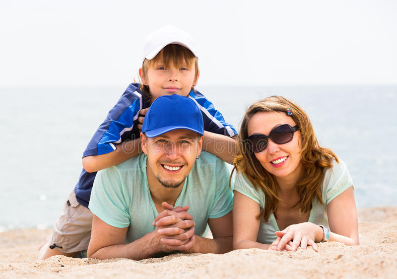 Familie mit Sohn am sandigen Strand stockbilder