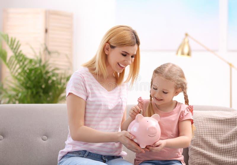 Familie mit Sparschwein und Geld stockbilder