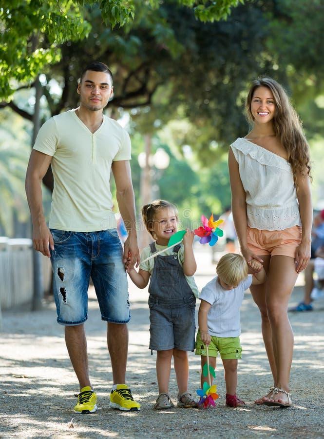 Familie mit Spielzeugwindmühlen am Park stockbilder