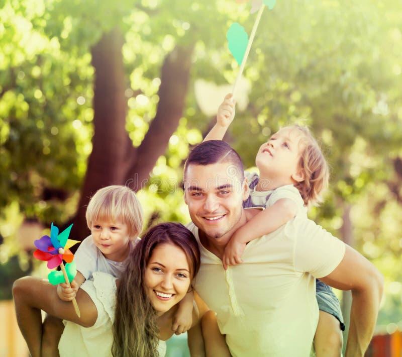 Familie mit Spielzeugwindmühlen am Park stockbild