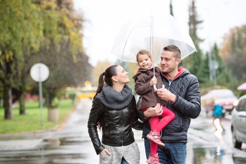 Familie mit Tochter unter den Regenschirmen gehen am regnerischen Tag lizenzfreie stockfotos