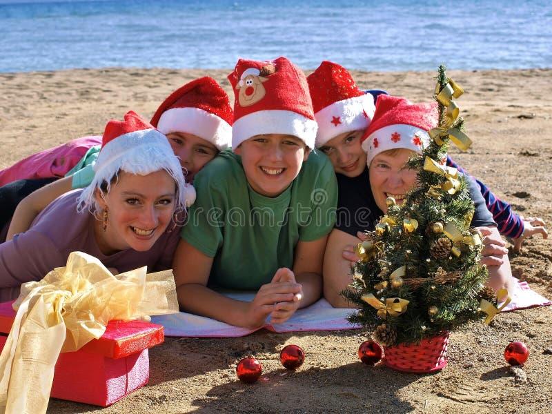 Familie mit Weihnachtsmann-Hut auf Strand stockfotos