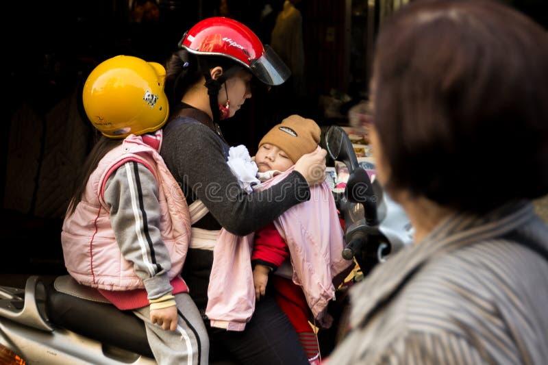 Familie mit zwei Kindern auf einem Motorrad, Mutter und ihren Kindern stockbilder