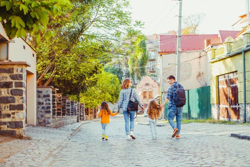 Familie mit zwei Kindern, die in die Stadt gehen stockbilder