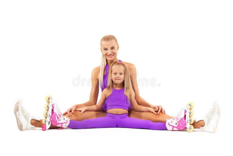 Familie, moeder en dochter, die in studio stellen die gealigneerde rollerskates dragen stock afbeelding