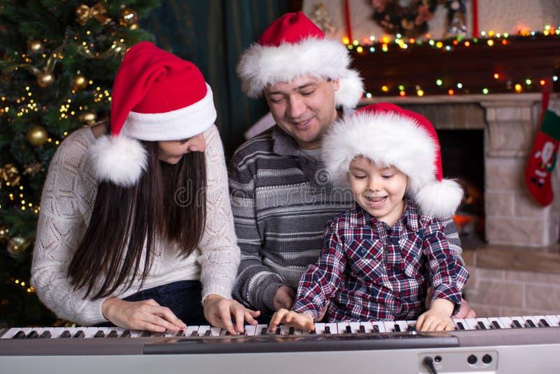 Familie - moeder, vader en jong geitje die santahoeden dragen die de piano over Kerstmisachtergrond spelen stock afbeelding