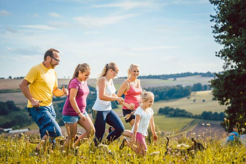 Familie, moeder, vader en jonge geitjes die voor sport lopen royalty-vrije stock fotografie