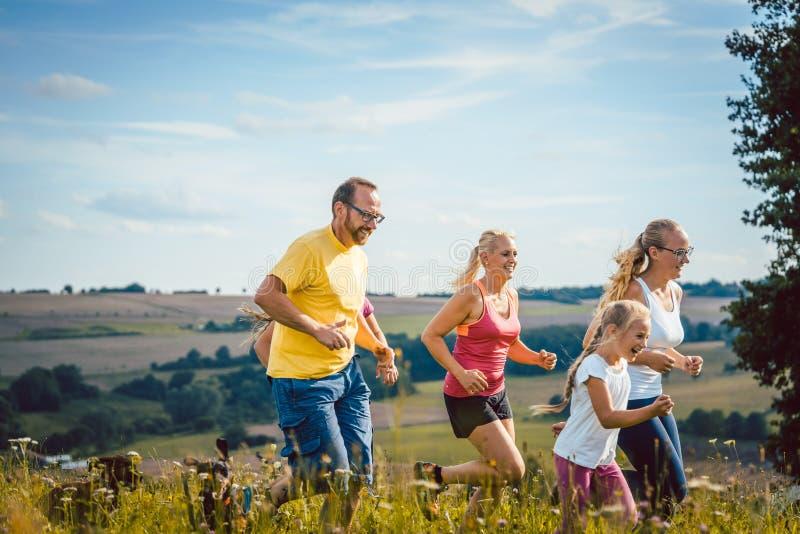 Familie, moeder, vader en jonge geitjes die voor sport lopen stock fotografie