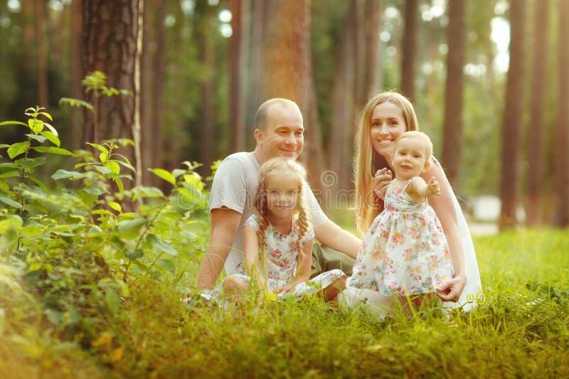 Familie - moeder, vader en van het twee dochtersblonde zitting in su stock fotografie