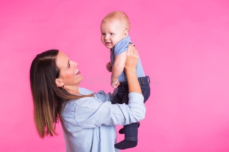 Familie, moederschap, ouderschap, mensen en kinderverzorgingconcept - de gelukkige moeder houdt aanbiddelijke baby over roze acht royalty-vrije stock fotografie