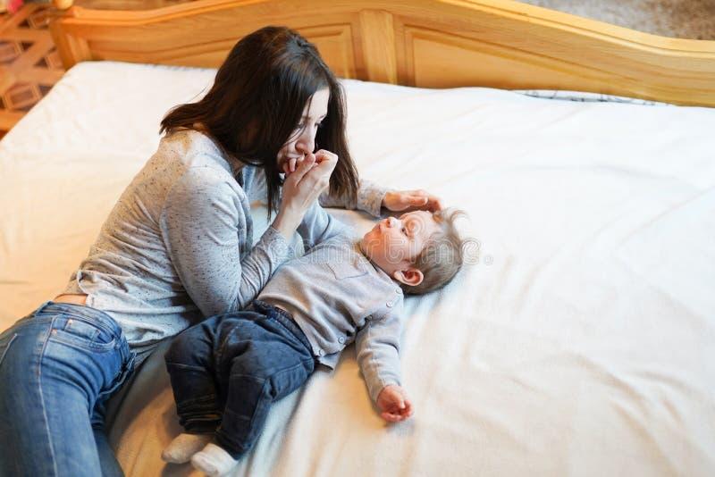 Familie, moederschap, ouderschap, mensen en kinderverzorgingconcept - gelukkige moeder die aanbiddelijke baby in slaapkamer kust royalty-vrije stock afbeelding