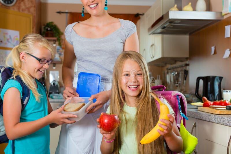 Familie - Mutter, die Frühstück für Schule bildet lizenzfreie stockfotos