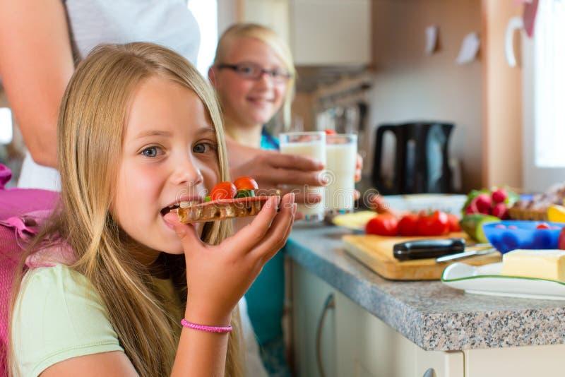 Familie - Mutter, die Frühstück für Schule macht lizenzfreie stockbilder