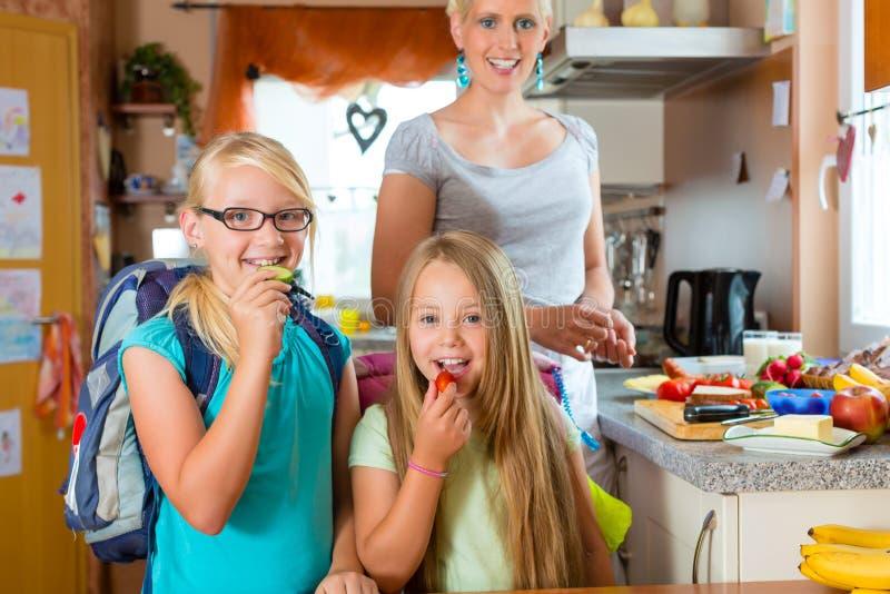 Familie - Mutter, die Frühstück für Schule macht stockbild