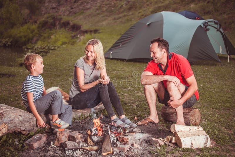 Familie nahe dem Feuer im Wald lizenzfreies stockbild
