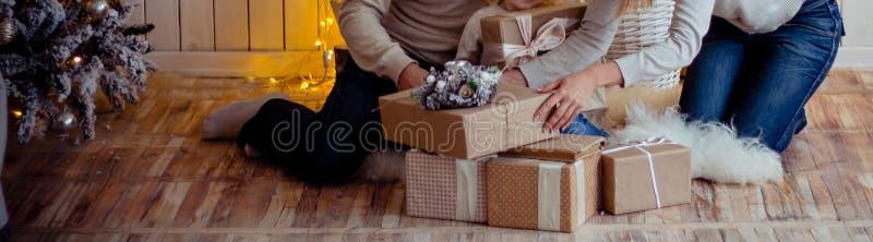 Familie nahe einem Kamin und einem Weihnachtsbaum analysiert die Geschenke, die auf dem Boden sitzen Familie nahe dem Weihnachtsb stockfotografie