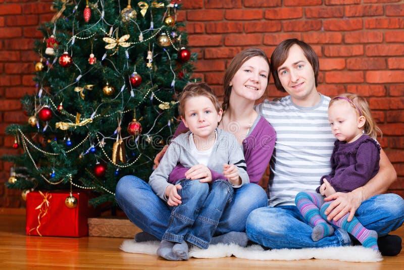 Familie nahe Weihnachtsbaum lizenzfreie stockbilder