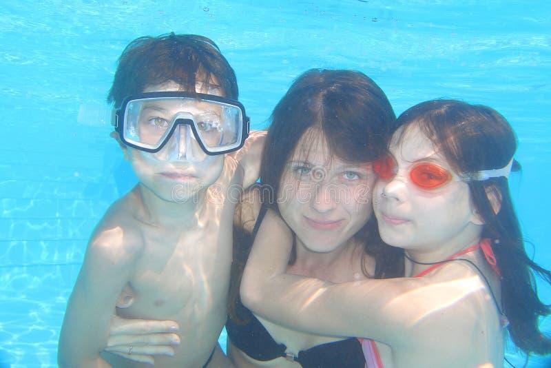 Familie onderwater in het zwembad stock afbeelding