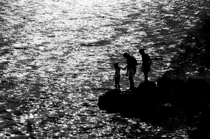 Familie op de rotsachtige kust stock afbeelding