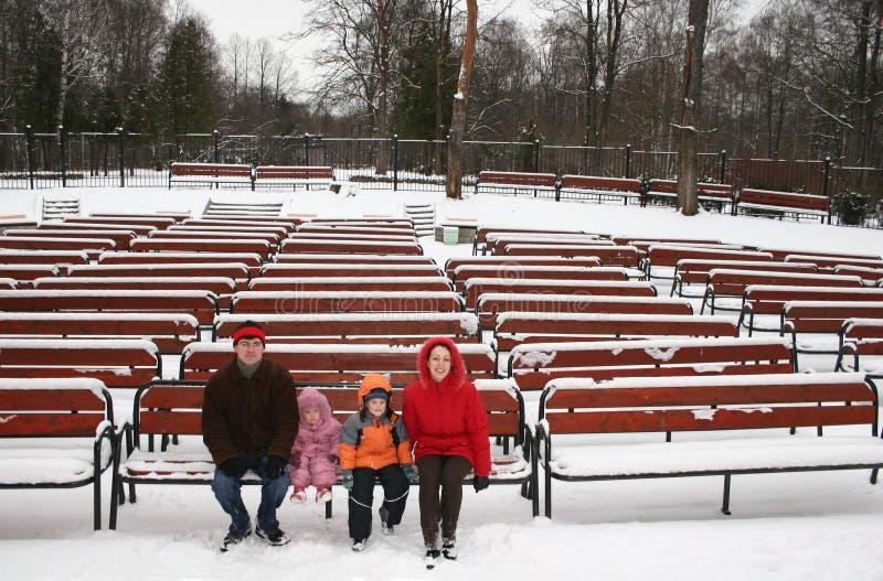 Familie op de winterbank royalty-vrije stock afbeeldingen