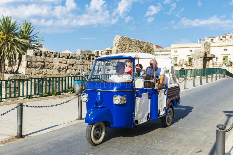 Familie op een driewieler in Siracusa, Sicilië, Italië stock foto's