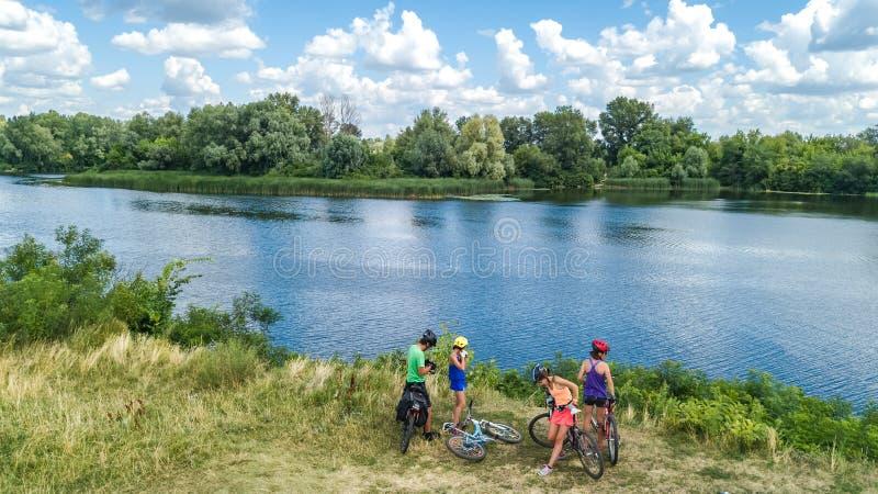 Familie op fietsen, actieve ouders en jonge geitjes die op fietsen, luchtmening van gelukkige familie met kinderen het ontspannen stock foto