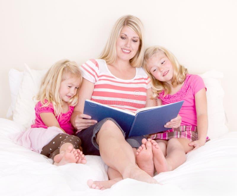 Familie op het boek van de bedlezing stock fotografie