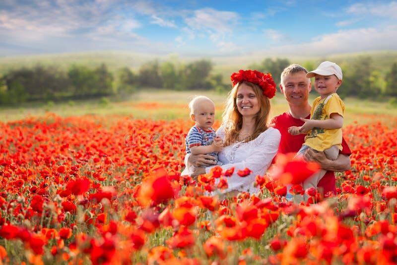 Familie op het gebied van rode papavers stock fotografie