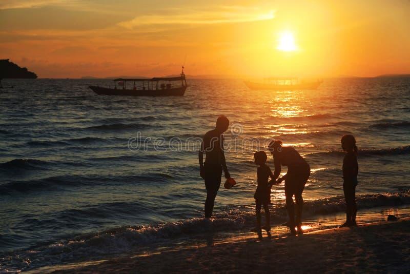 Familie op het strand bij zonsondergang royalty-vrije stock foto