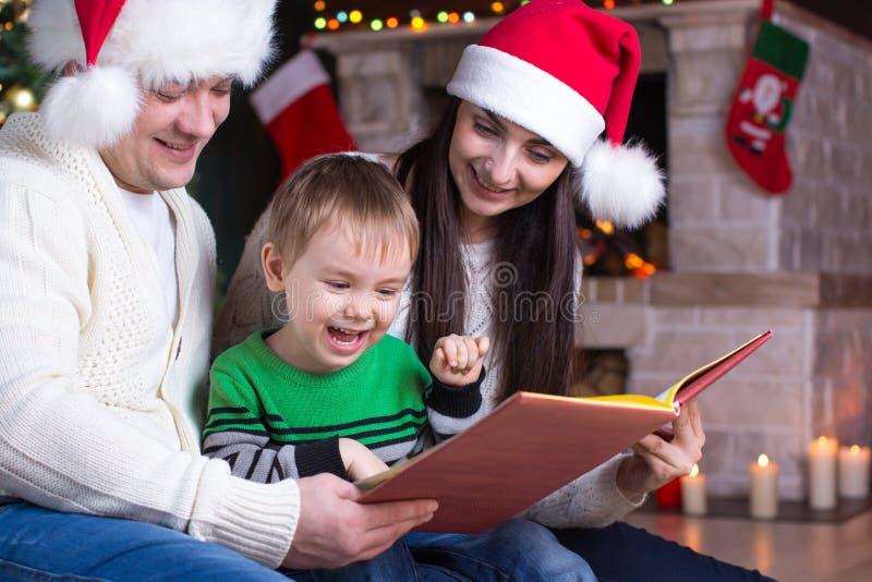 Familie op Kerstavond door de open haard die een boek lezen aan hun kind royalty-vrije stock afbeeldingen