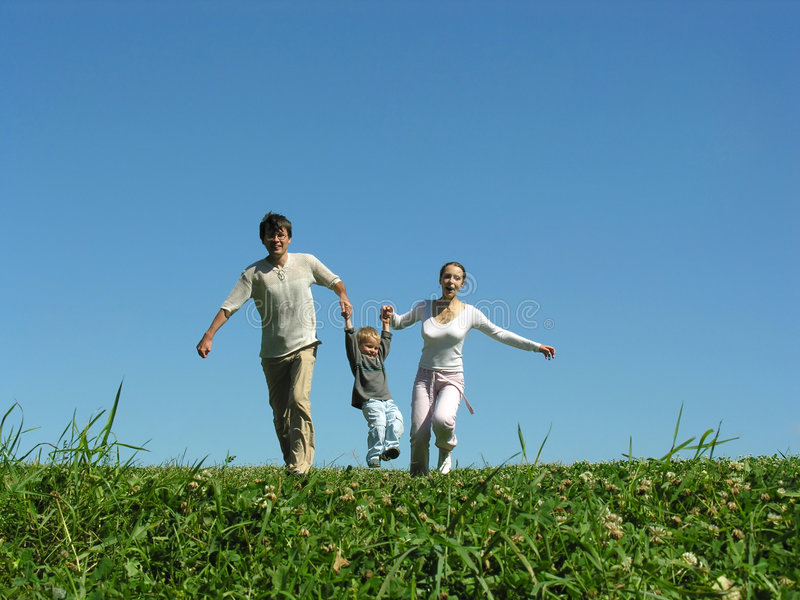 Familie op kruid onder blauwe hemel stock afbeeldingen