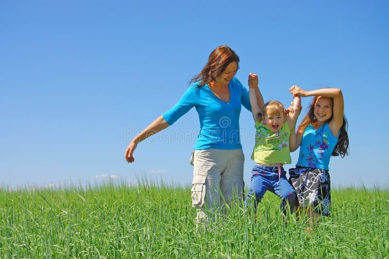 Familie op kruid onder blauwe hemel stock foto