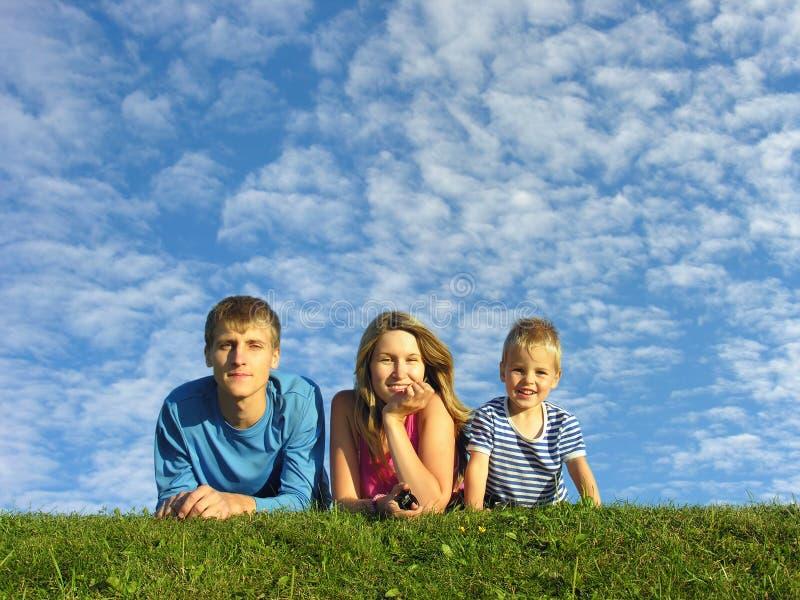 Familie op kruid onder blauwe wolkenhemel stock afbeelding