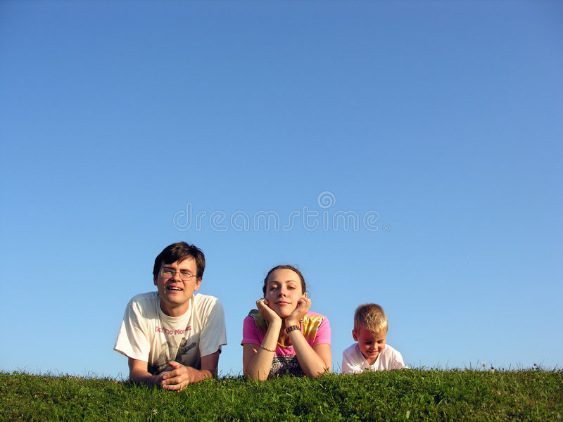 Familie op kruid onder hemel 2 stock afbeelding