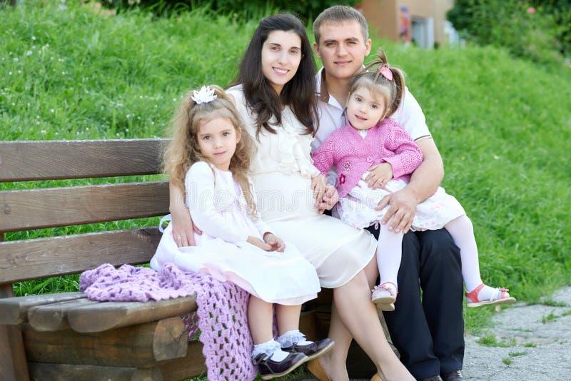 Familie op openlucht, zwangere vrouw met kind en de mens, stadspark, zomer, groene gras en bomen stock afbeelding