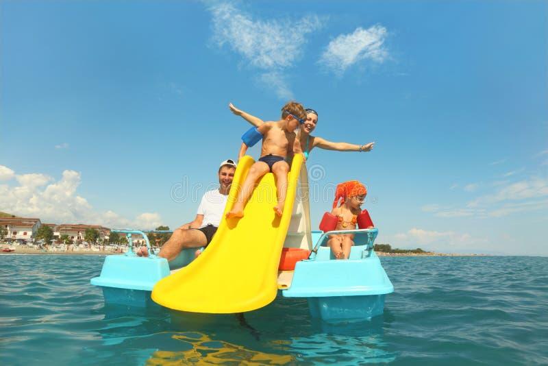 Familie op pedaalboot met gele dia in overzees stock foto's