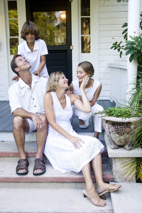 Familie op portiekstappen stock afbeelding