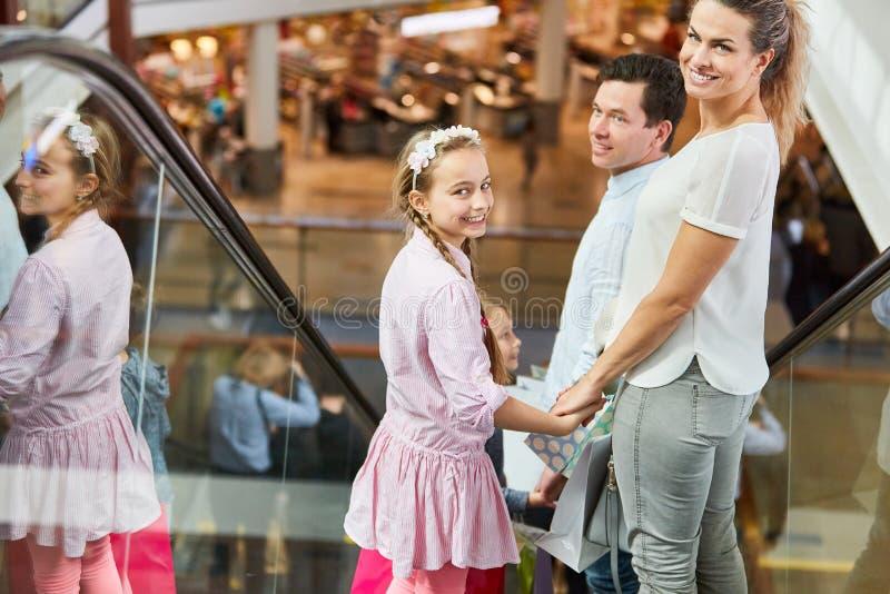Familie op roltrap in winkelcomplex stock fotografie