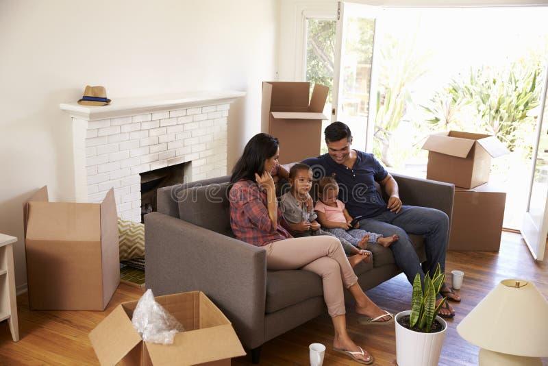 Familie op Sofa Taking een Onderbreking van het Uitpakken van het Letten op TV stock afbeeldingen