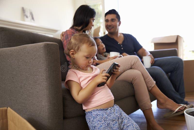 Familie op Sofa Taking een Onderbreking van het Uitpakken van het Letten op TV royalty-vrije stock fotografie