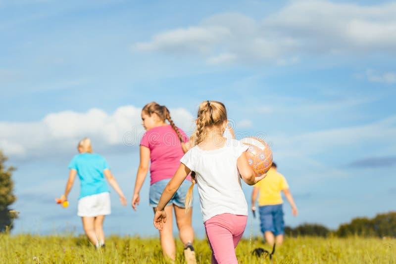 Familie op speelse wijze op een weide in de zomer stock foto's