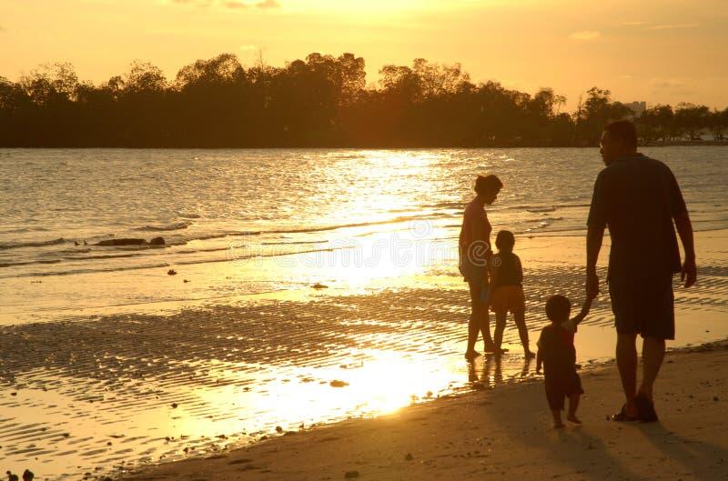 Familie op zonsondergangstrand stock foto