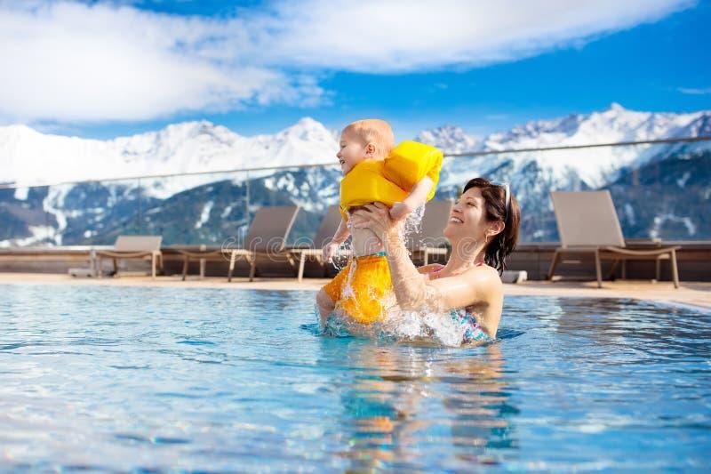 Familie in openlucht zwembad van alpiene kuuroordtoevlucht royalty-vrije stock afbeelding