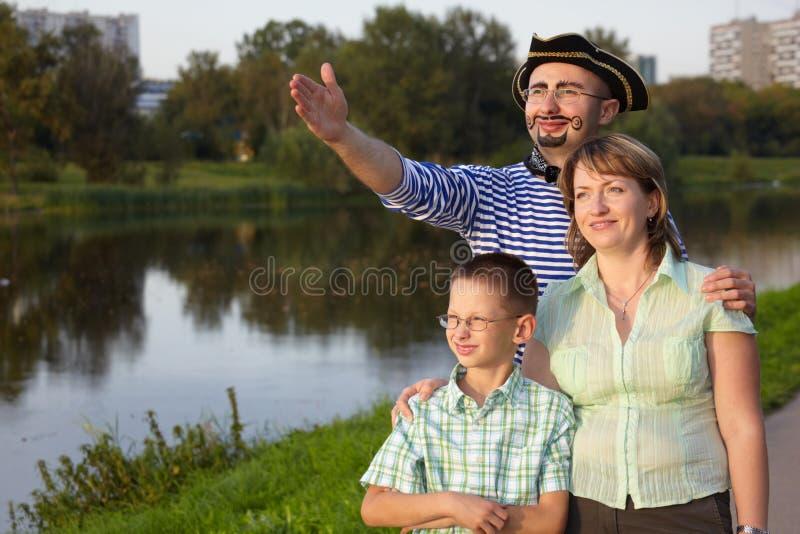 Familie in park dichtbij vijver: mens in piratkostuum royalty-vrije stock afbeeldingen