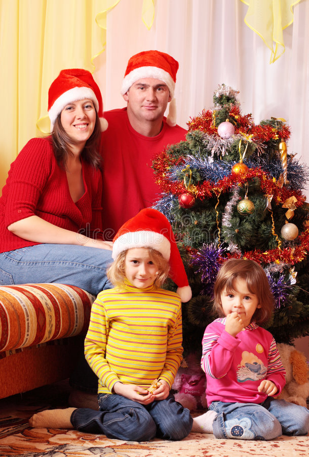 Familie in rode Kerstmishoed stock afbeelding