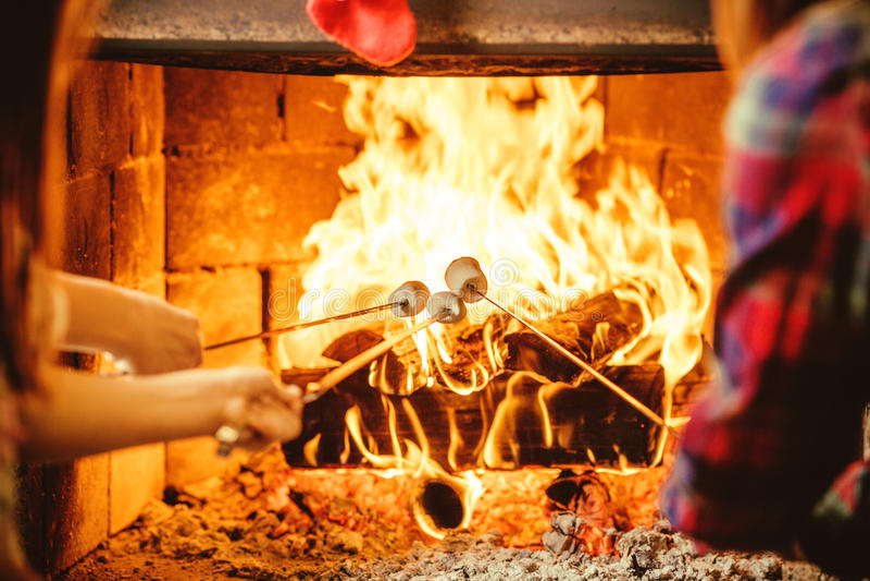 Familie roosterende heemst door de brand Comfortabel chalethuis met stock foto's