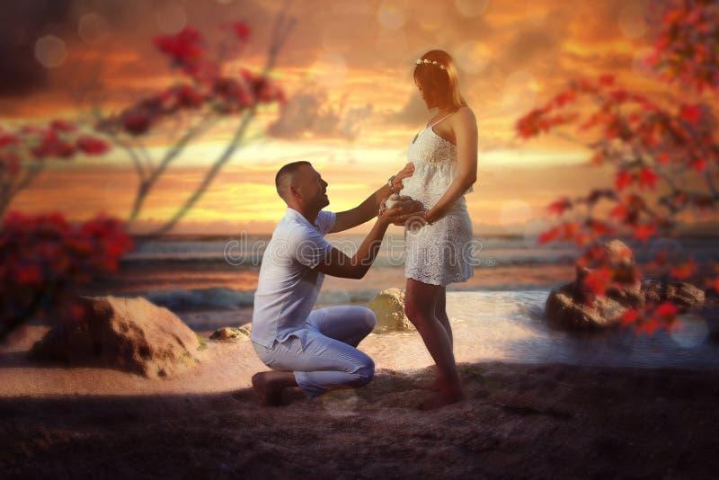Familie samen bij het strand De vrouw is zwanger stock afbeelding