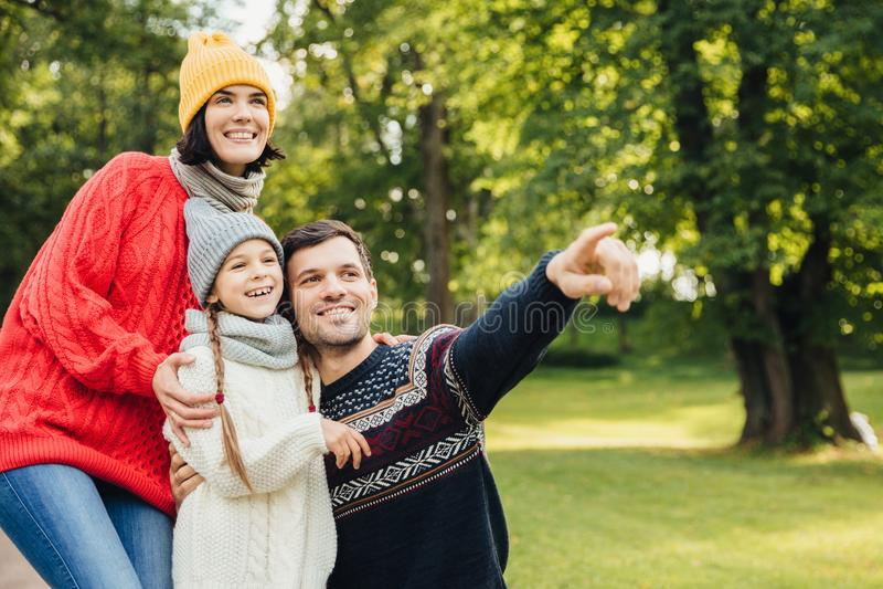 Familie, seizoen, verhoudingsconcept De vriendschappelijke hartelijke familie heeft gang bij de herfstpark, bewondert mooie aard, stock afbeeldingen